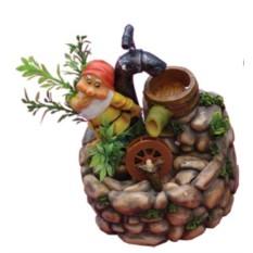 Фонтан Гном стоит спиной к крану, с колесом в кустах